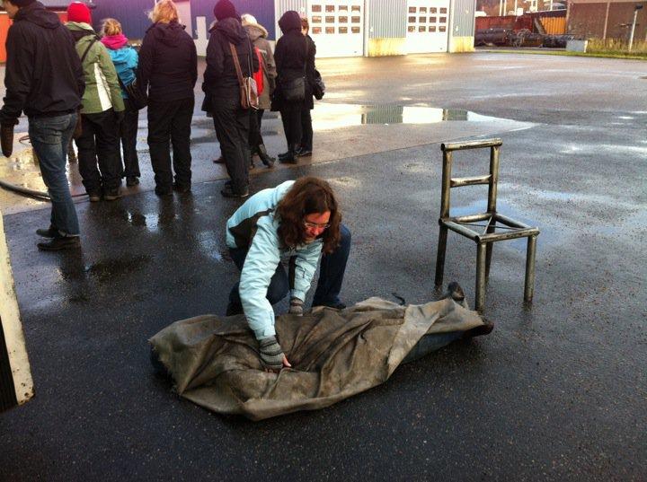 Eva-Lena täcker över dockan som brinner med en brandfilt!